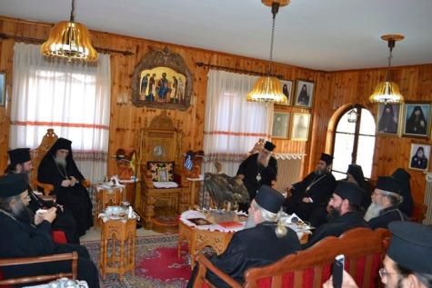 """7/20 martie 2014: Întâistătătorul noii structuri sinodale, Calinic, dimpreună cu Chiprian al II-lea, mitropolitul fostului grup sinodal cunoscut sub numele de """"chiprianit"""", stând de-a dreapta şi de-a stânga tronului arhieresc din arhondaricul Mănăstirii de la Fili, pe care tronează fotografia fostului întemeietor Chiprian."""